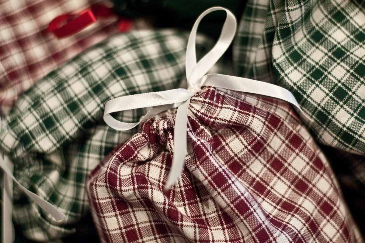 Reusable fabric gift bags in red and green plaid with white ribbon bow