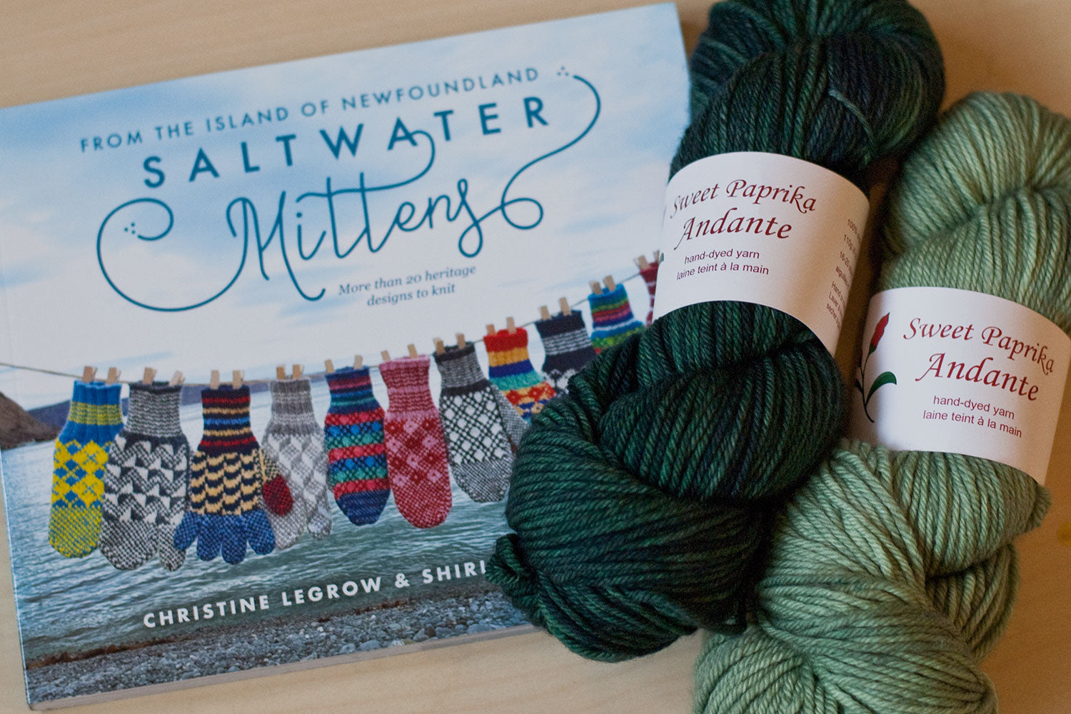 Saltwater Mittens book with two skeins of hand-dyed yarn in sage green and dark greenand-dyed yarn