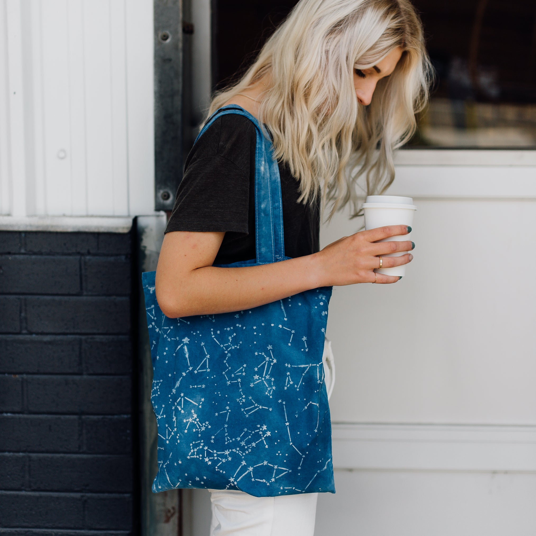 Woman carrying take-out coffee and wearing shoulder bag dyed using clay resist and a stencil to create constellation patterns