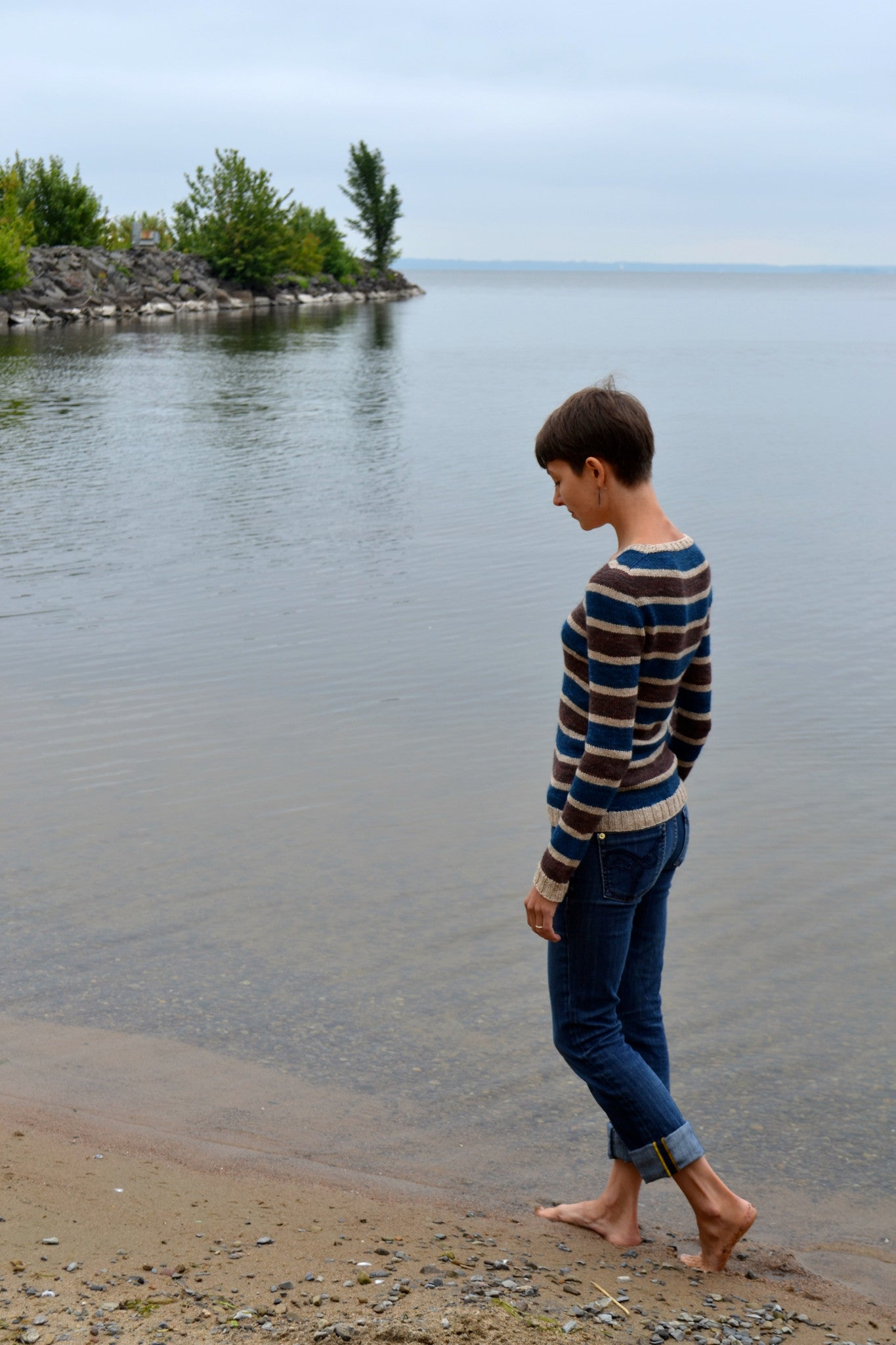 Stillness knitting pattern worn with jeans on the beach