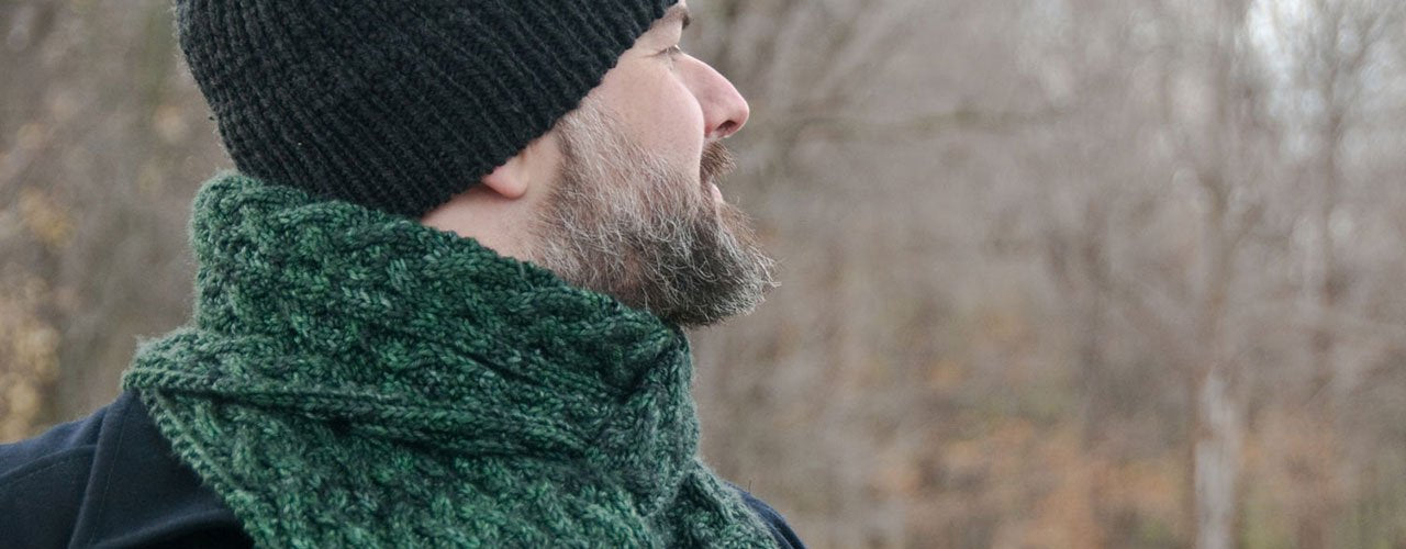 man wearing green reversible cable knit scarf wrapped around neck