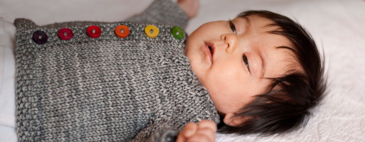 Baby cardigan with patterned yoke and rainbow buttons