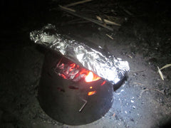 Marc Gauthier using his Sidewinder Ti-Tri in wood burning mode to cook trout in a foil pouch on the Wind River Range