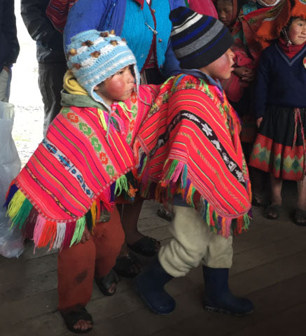 boys in red ponchos; Andean boys in regional ponchos