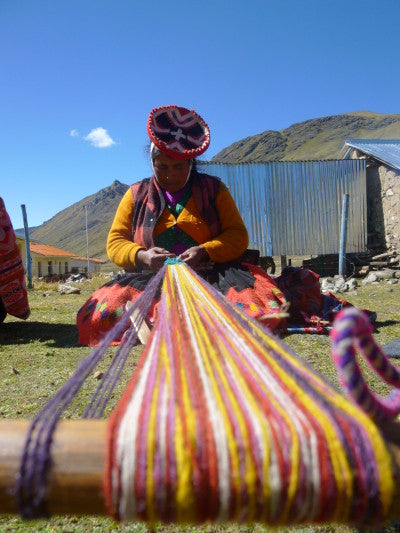 Eugenia Huaman Quispe, warping and weaving vibrantly colored guitar straps for an order pickup in July