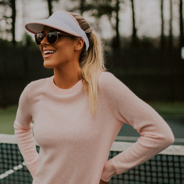 woman wearing visor and sunglasses