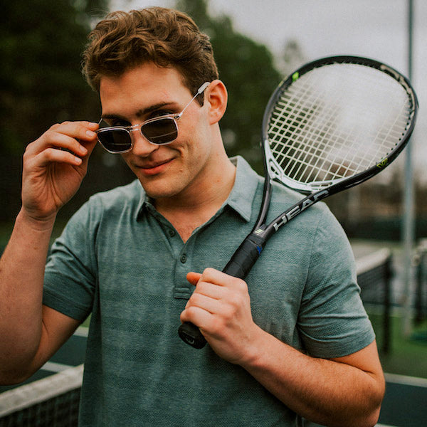 Man holding tennis racket wearing shades
