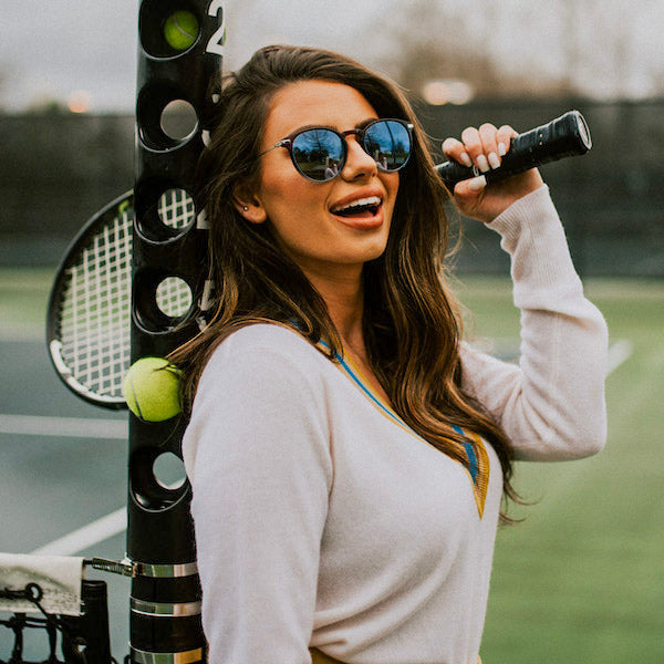 Woman holding tennis racket wearing sunglasses