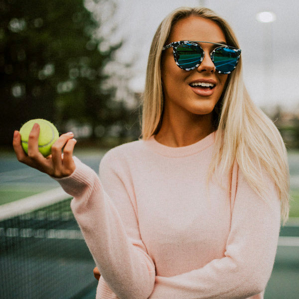 woman holding tennis ball wearing marble shades