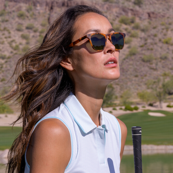 woman golfing wearing sunglasses