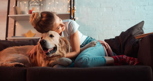 Girl hugging golden retriever dog on couch