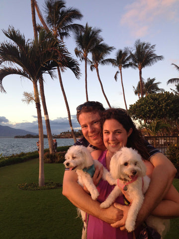 James and Molly holding their two dogs on grass next to the ocean