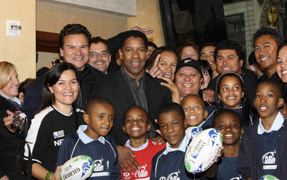 Denzel Washington greets a team of youth from the Bronx and sports stars from New Zealand
