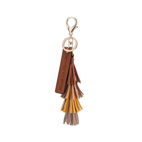 vegan, cruelty free, handbag, bag, purse, faux leather, animal friendly, sustainable fashion, keychain, gold hardware, quote, escape the ordinary, saddle, brown, tassel