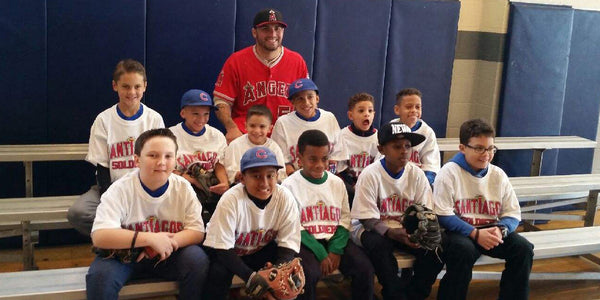 Hector Santiago poses with a group of Santiago's Soldiers, an inner-city Little League group.