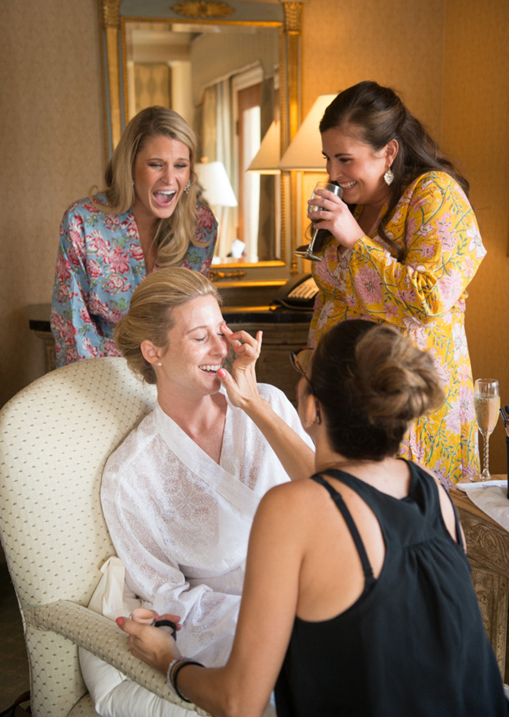 bride and bridesmaids laughing getting ready