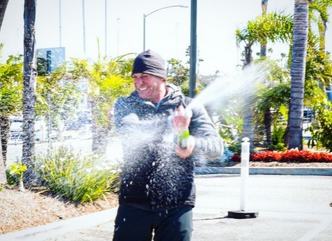 Frasca celebrates with a spray of bubbly upon completing his world record Cannonball Run.