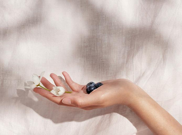 An open hand holds small flowers with blueberries against a Blush Linen Flat Sheet backdrop.
