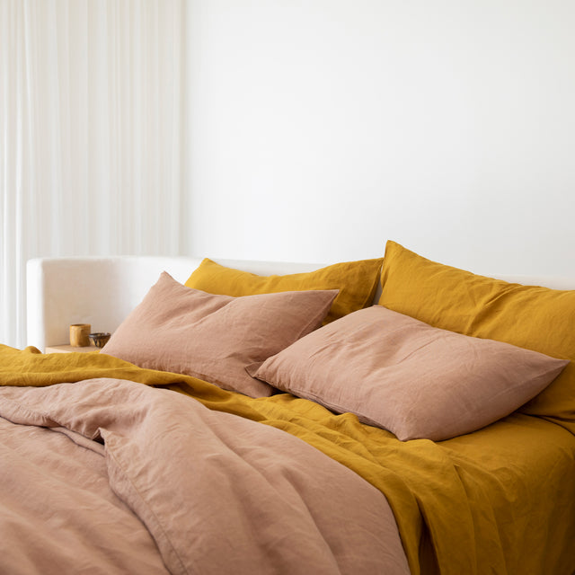 A bed styled with a Linen Duvet Cover Set in Fawn and a Linen Sheet Set with Pillowcases in Mustard.