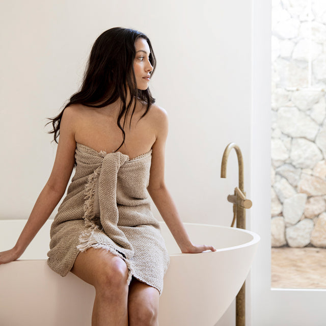 A model with fair skin and dark hair sitting on the edge of a bathtub. She has a Pure Linen Towel in Natural wrapped around her.