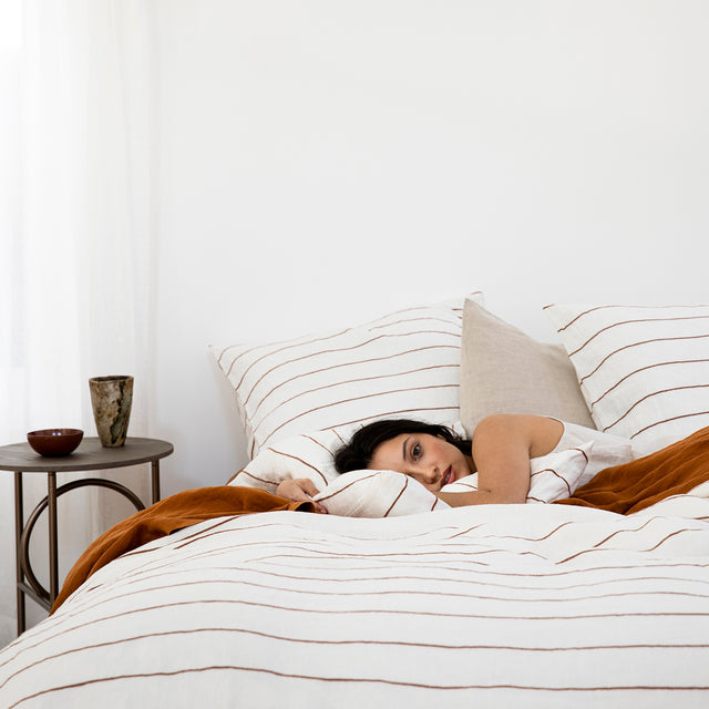 Model lying in bed with linen bedding in Cedar Stripe, Cedar flat sheet and Natural pillowcase