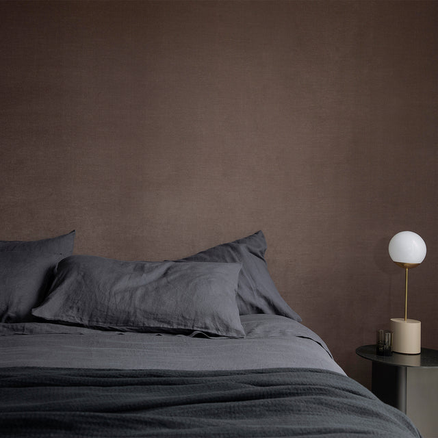 A bed that is styled with CULTIVER Slate linen, including a Duvet Cover, Fitted Sheet and Pillowcases. Next to the bed is a gray bedside table with a lamp.