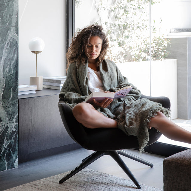 Model sitting and reading a book while wearing the Estela Linen Waffle Throw in Forest color