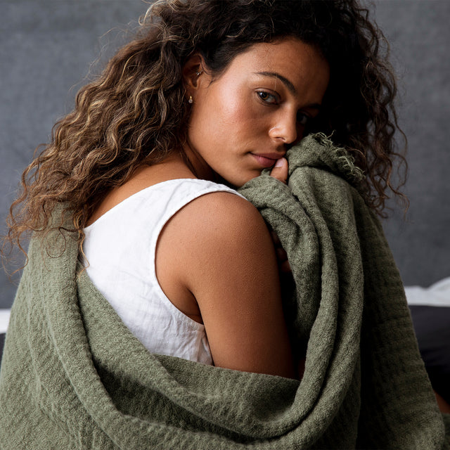 Model with Estela Linen Waffle Throw in Forest color wrapped around herself