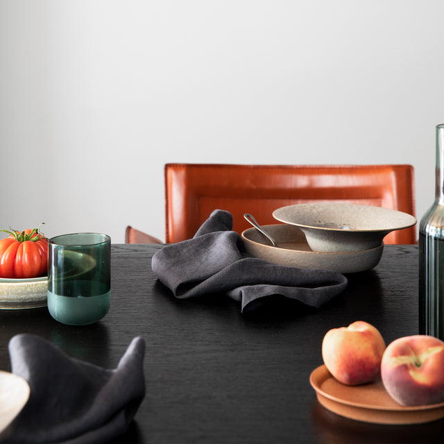 A dark brown wooden table styled with various ceramic bowls, fruits and the Linen Table Napkins in Slate.