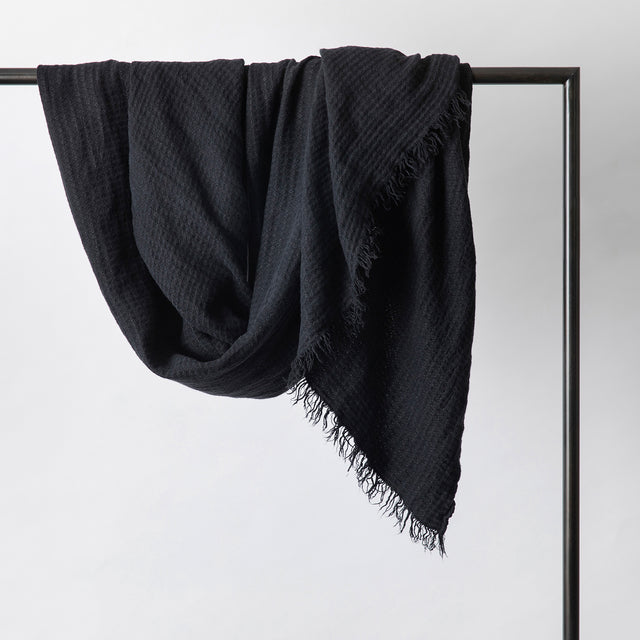 Estela Linen Waffle Throw in Black hanging on a rail