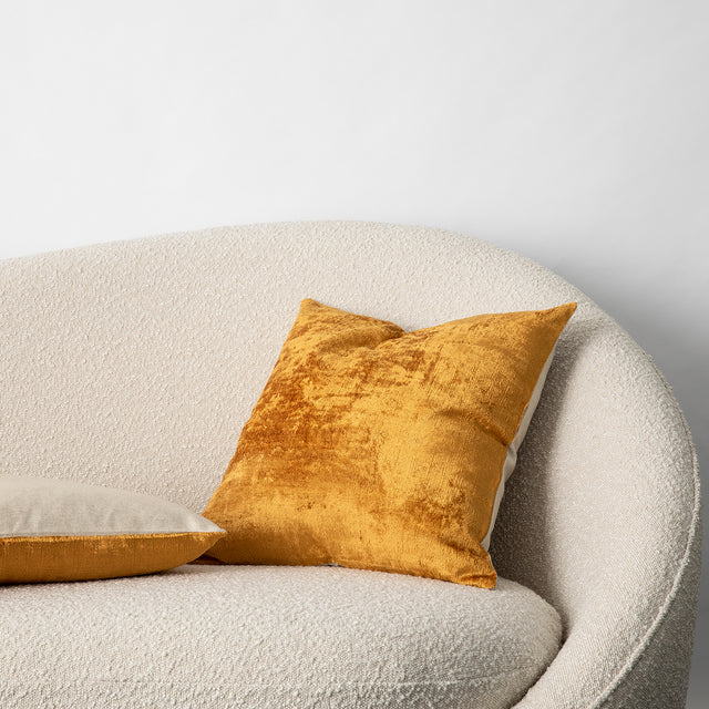 The Talik Velvet Cushion in Mustard on a boucle lounge.