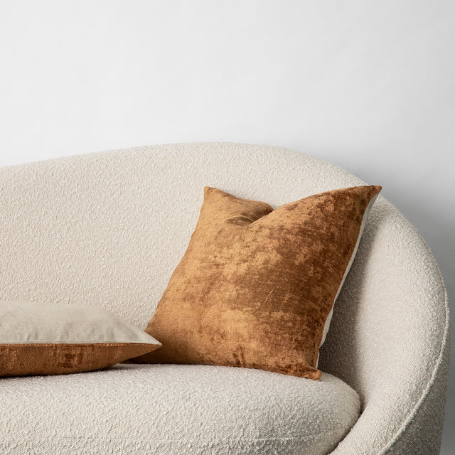 The Talik Velvet Cushion in Fawn on a boucle lounge.