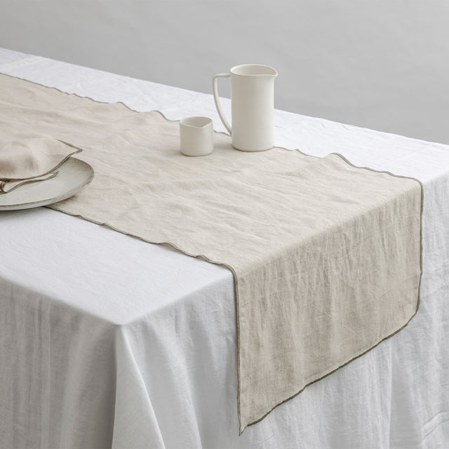 Cara Edged Table Runner in Olive on a Linen Tablecloth in White