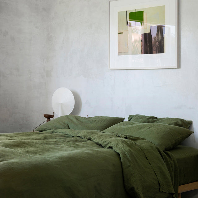 Bed styled with Forest Duvet Cover Set and Forest Sheet Set. On the wall there is a painting, and on the bedside table is a lamp and small ceramic.