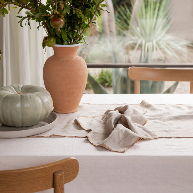 A table dressed in the Cara Panel Tablecloth, Cara Edged Table Runner and 1 Cara Edged Napkin in Natural. On top of the table linen is a terracotta vase of pomegranates and a large pumpkin on a gray plate/dish.