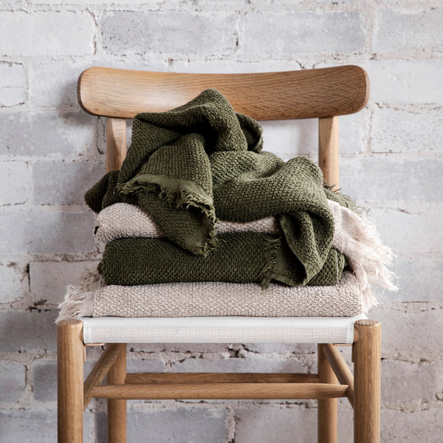 A stack of styled Pure Linen Bath Towels in Natural and Forest on a wooden chair.