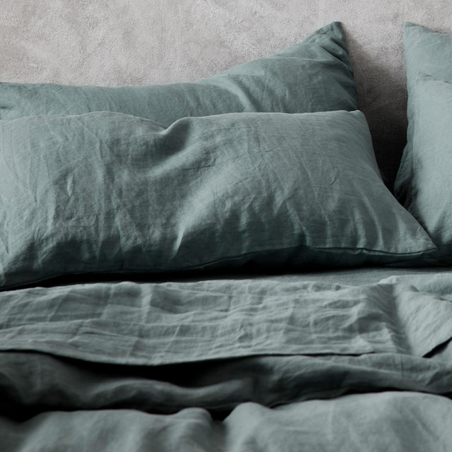 A close up on the Set of 2 Linen Pillowcases  and Duvet Cover Set in Bluestone on a bed.