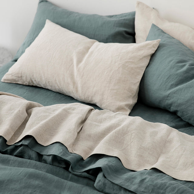 A close up of a bed styled in a Set of Linen Pillowcases, Linen Flat Sheet in Natural, Linen Sheet Set and Duvet Cover in Bluestone.