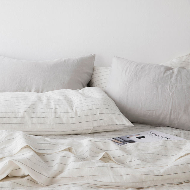 A bed styled with a Pencil Stripe Duvet Cover, Fitted Sheet and Pillowcases, and Smoke Gray Pillowcases.
