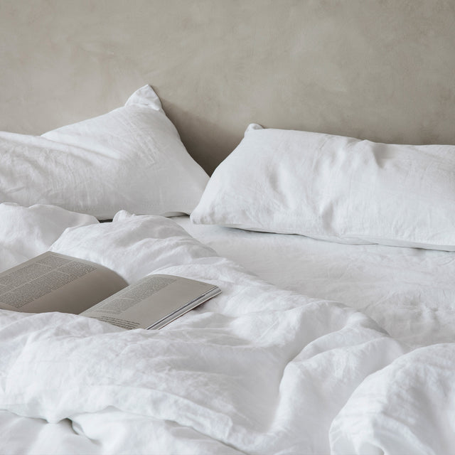 A bed in front of a beige textured wall. The bed is dressed in white linen, and has an open book resting on top.