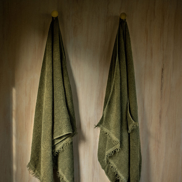 Two Forest Pure Linen Bath towels hanging on wall.
