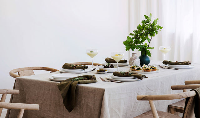 A table setting with white crockery and dark cutlery styled with a Linen Tablecloth in Natural and Linen Table Napkins in Olive amongst a plate of entrees, cocktails and 2 vases, one of which contains some branches.