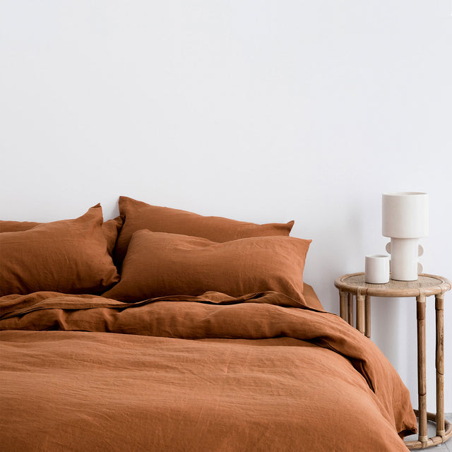 Bed styled with Cedar duvet cover set and Cedar sheet set. On the cane bedside table is a white ceramic lamp and coffee cup.