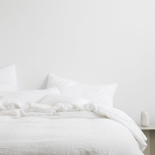 Bed styled with White Linen Duvet Cover Set and White Linen Sheet Set. On the bedside table there is a simple white ceramic vase.