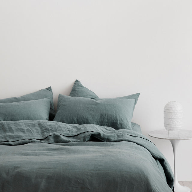 Linen Duvet Cover Set and Linen Sheet Set in Bluestone styled on bed.