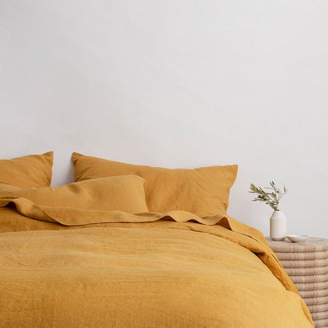 Bed styled with Mustard Duvet Cover Set and Mustard Sheet Set. On the bedside table is a ceramic with small foliage in it and a small dish.