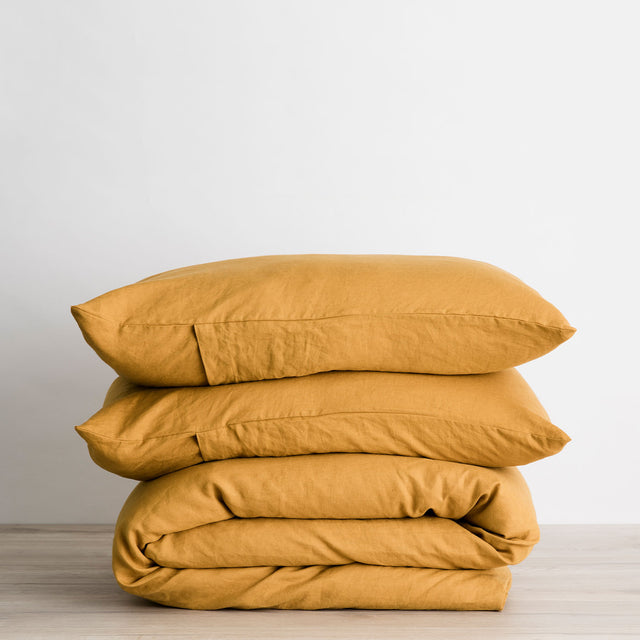 Linen Duvet Cover Set in Mustard folded and stacked.