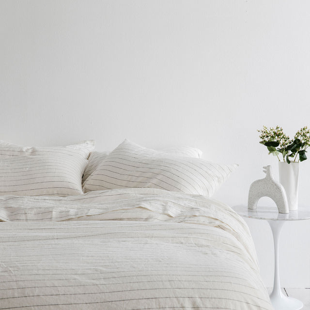 Bed styled in Linen Duvet Cover Set and Linen Sheet Set in Pencil Stripe. On the bedside table is a ceramic vase with flowers and ceramic object.