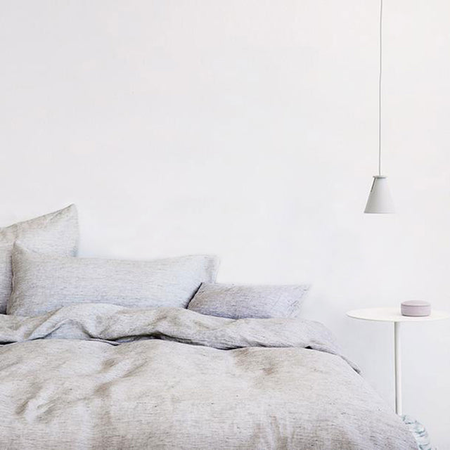 Bed styled with Pinstripe Duvet Cover Set and Pinstripe Sheet Set. A pendant light hangs over the bedside table.