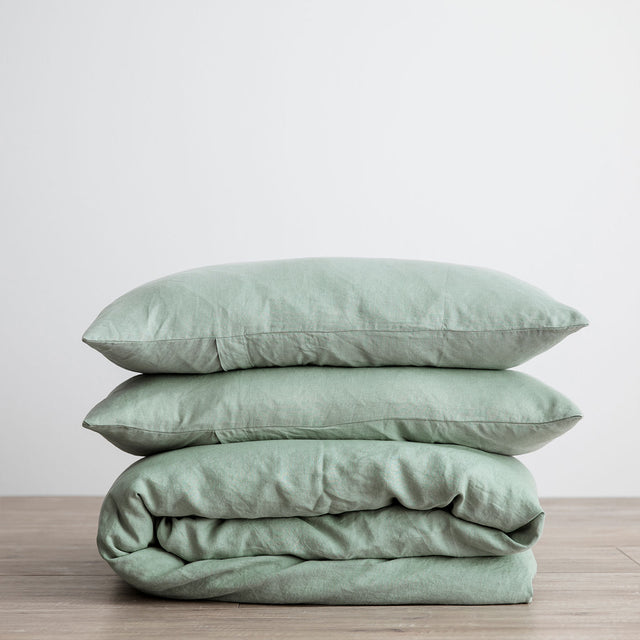 Linen Duvet Cover Set in Sage, folded and stacked.